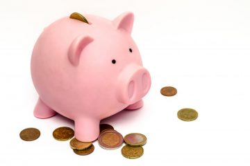 white background with pink piggy bank and coins laying around