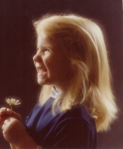 young girl in a blue dress with long blonde hair holding a daisy smiling